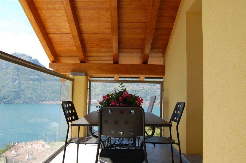 Balcón con vista al lago y muebles de jardín