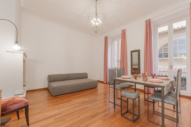 Sweet pastel colors livingroom, with large sofa double bed, fireplace and 2 big windows and balcon