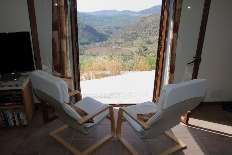 Looking out the glass doors in the lounge, towards the private terrace and over the olive grove