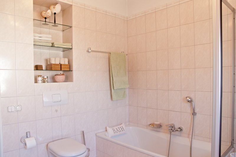 Spacious and bright bathroom with shower and bath tub