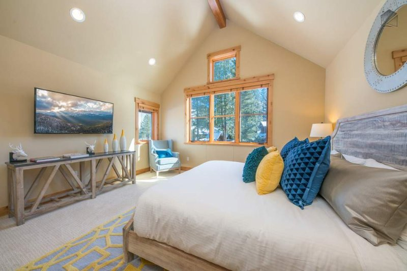 The Master Bedroom is beautifully lit by natural light, and has a California King bed and a TV.