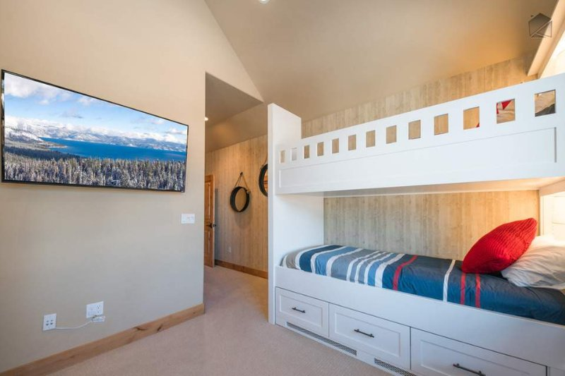 A wide screen TV is mounted to the wall on the far end of the bunk room.