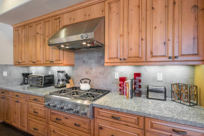 A 6-burner professional grade gas range and hood are exquisitely placed within the wood cabinetry.