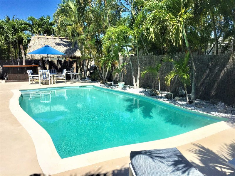 Pool and deck area is surrounded by lush tropical landscaping.