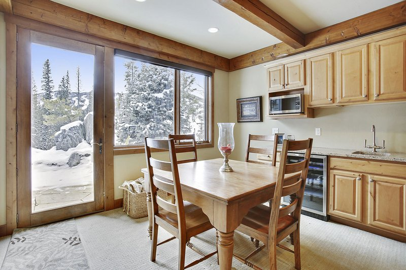 Lower level dining area with bar and microwave with direct access to outdoor fire pit and hot tub