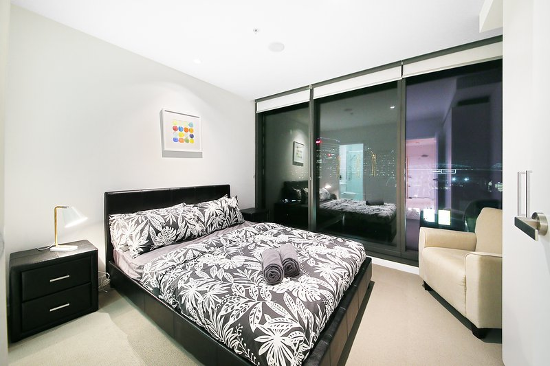 A master bedroom with a queen sized bed & plush pillows.