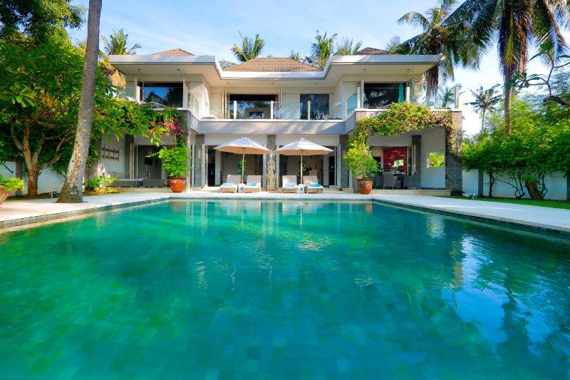 Grande piscina com espreguiçadeiras, rodeado por vegetação tropical
