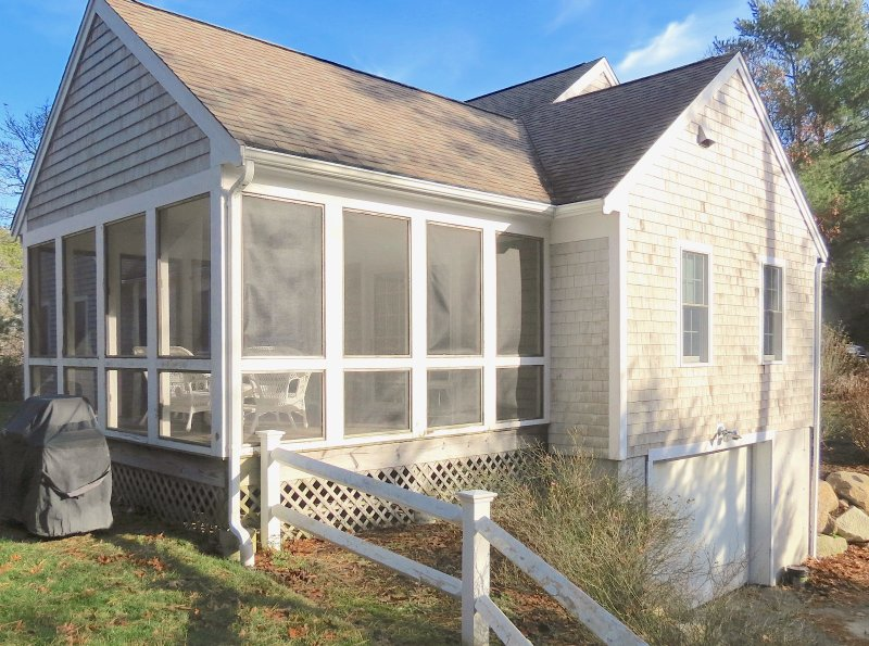 Roomy, comfortable screened porch is a special feature of this appealing Brewster vacation home.