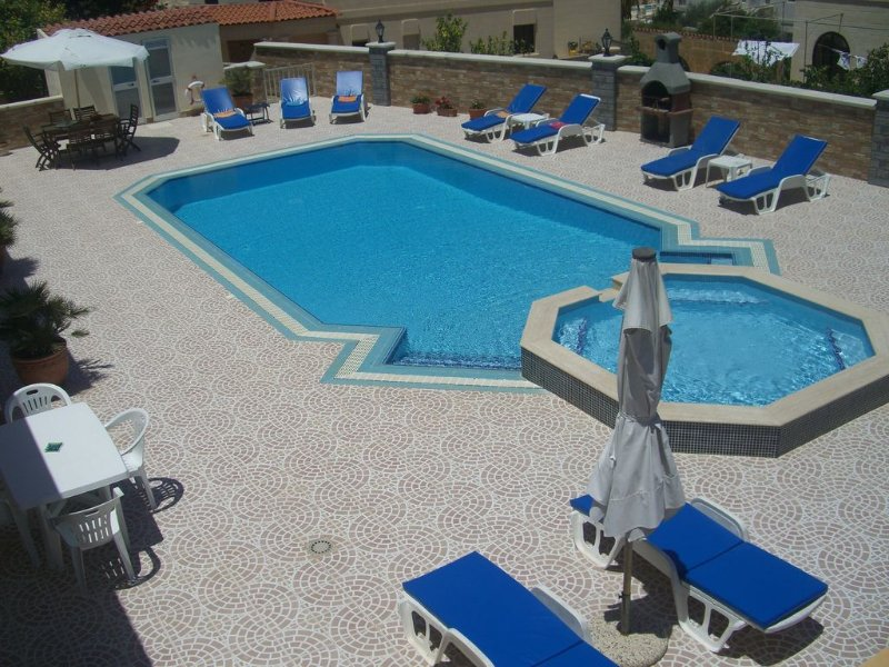 Swimming pool with surrounding terrace.