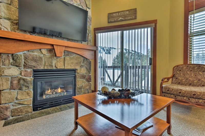A magnificent stone fireplace highlights the living room.