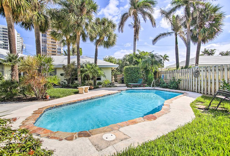 This home is highlighted by a wonderful pool, backdropped by palm trees.