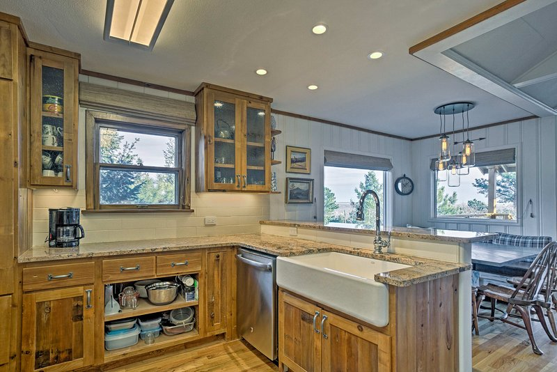 This kitchen is adorned with a farmers sink, warming drawer, breakfast bar and stainless steel appliances.