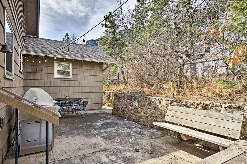 This patio boasts a gas grill, wooden benches and an outdoor table with seating for 4.