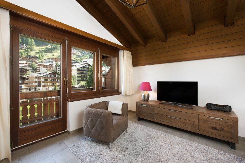 The living room features a smart flat screen TV and Bluetooth speakers.