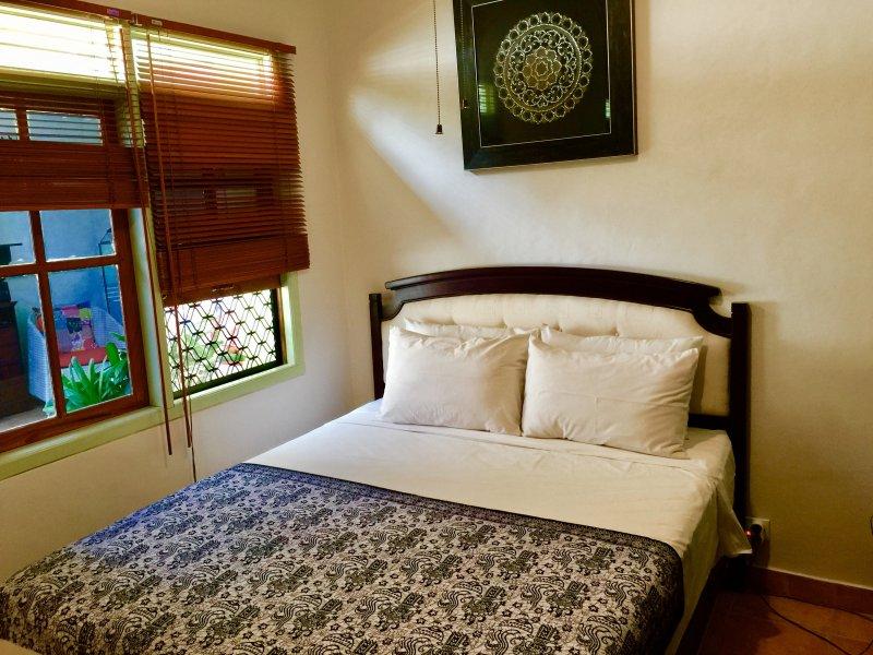 Chambre de la Reine, avec placard, placard tallboy, table de chevet, ventilateur de plafond Tamp, vue sur la piscine, l'air conditio