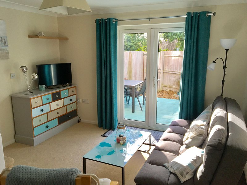 Sitting room with access to decking in private enclosed area and gate to rear parking. Seats Four.