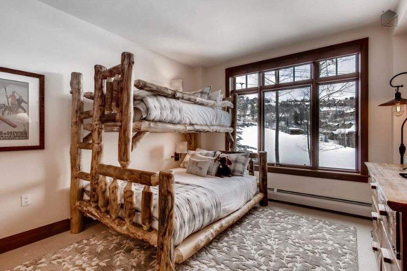 As colchas e saudáveis e beliches de madeira natural adicionar ao cenário de montanha idílico para fora da janela.