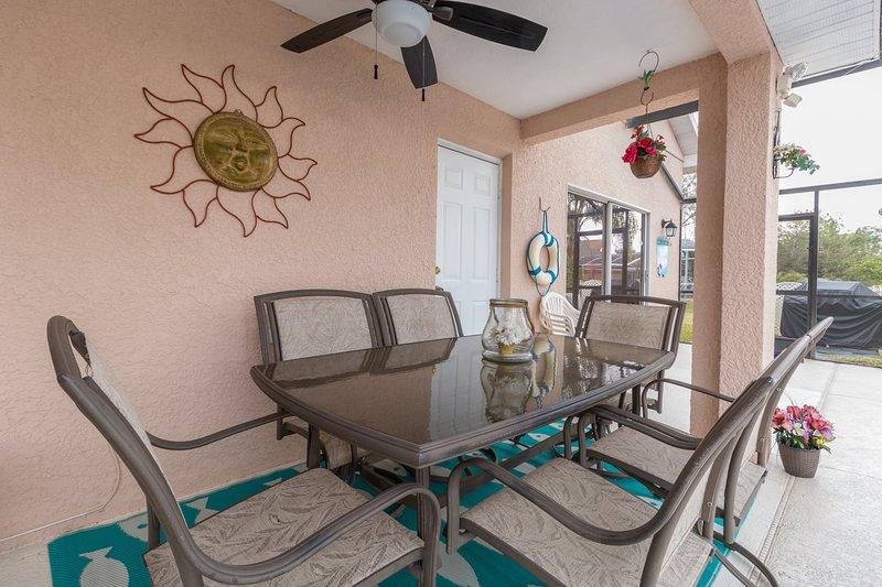 Veranda con mesa, sillas y ventilador de puerta.