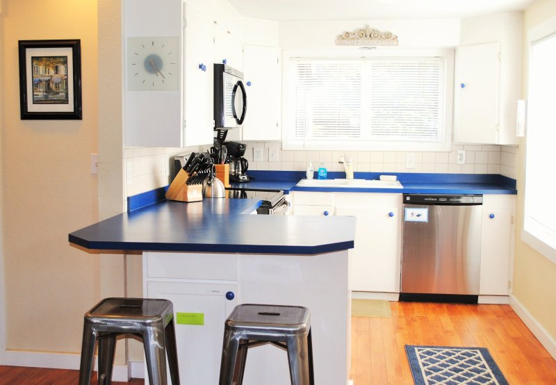 Kitchen room with stove, fridge, microwave, and small appliances