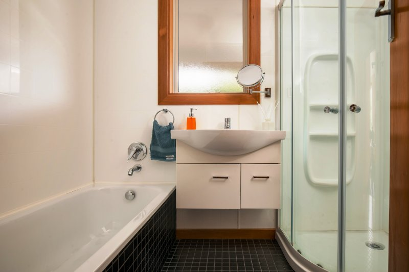 A fully renovated bathroom with bath, shower, basin and toilet.