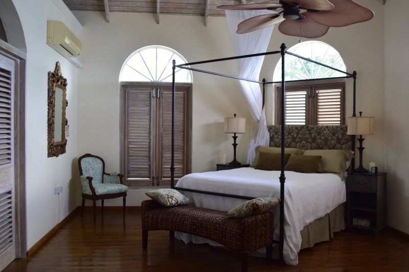 Spacious master bedroom suite with bronze canopy queen bed and soaring ceilings