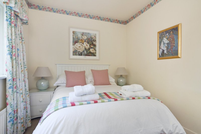 The Calico Room with standard double bed.  Print of calico flowers above bed.