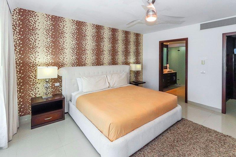 Primera suite principal con cama king, vista al mar, televisión de alta definición con reproductor de DVD y satélite