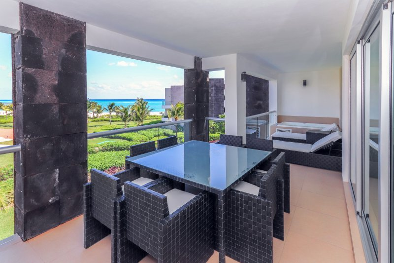 Vista al mar terraza con jacuzzi, sillones y mesa de patio con capacidad para 8
