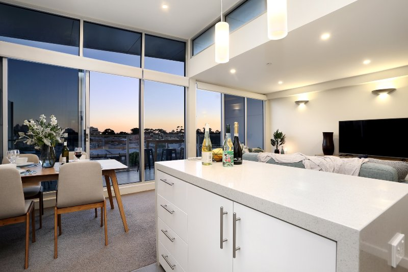 Serviced apartments brunswick - kitchen with dining and lounge areas in background