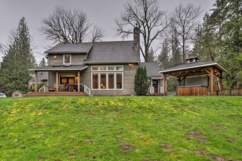 This 5-acre property boasts a large deck, private hot tub, and river views.