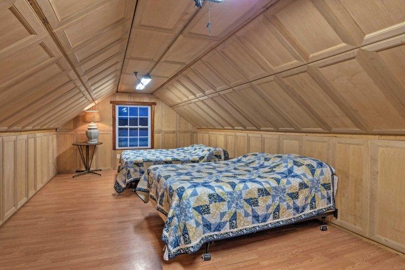 La habitación del segundo piso tiene una cama de matrimonio y una cama de matrimonio.