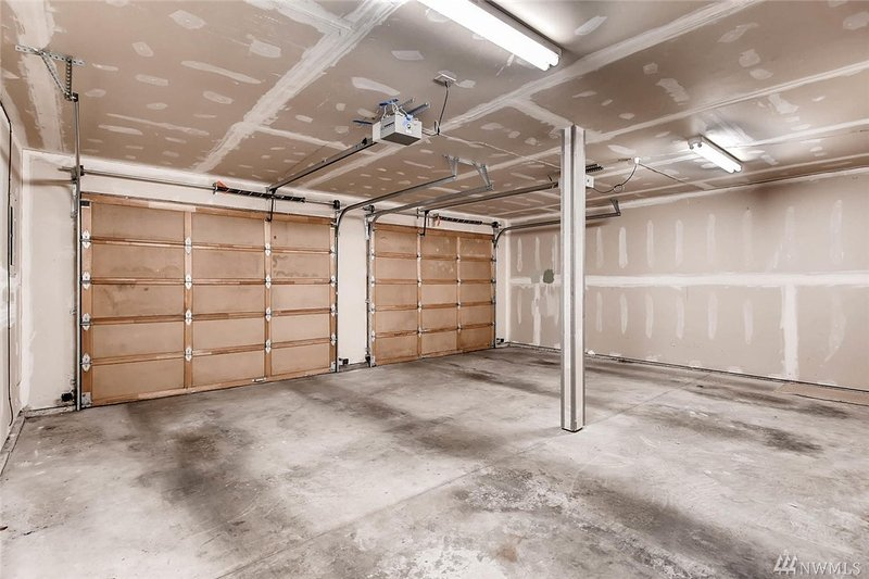 A large 2 car garage has plenty of space for 2 cars and 2 additional cars can be parked outside it