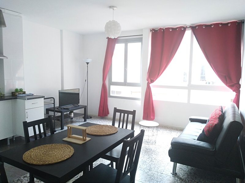 living room with kitchenette and large windows.