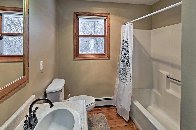 El baño completo está equipado con un combo de ducha / bañera y la vanidad individual pintoresco.