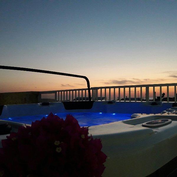 bañera de hidromasaje con la puesta de sol en el fondo