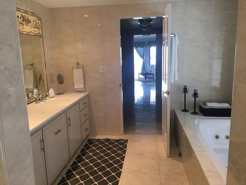 baño principal con doble lavabo y bañera de hidromasaje y vestidor fuera de él para la facilidad de cambiar.