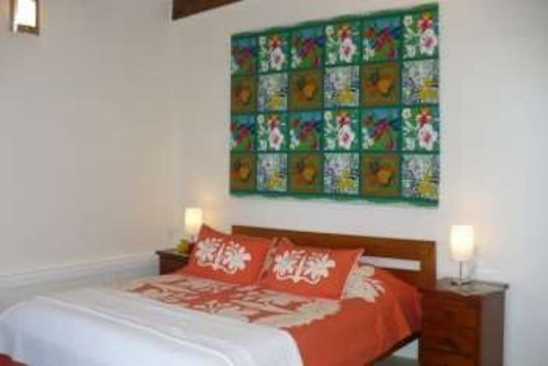 The kingsize bed, table lamps, and side tables in the Reef View