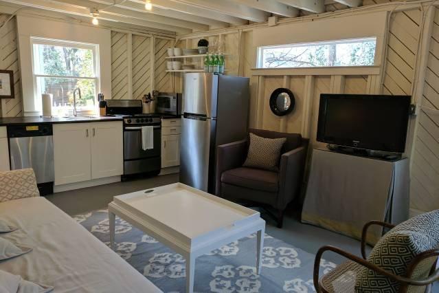 coin salon avec cuisine américaine, canapé-lit complet et d'une télévision équipée de Roku.