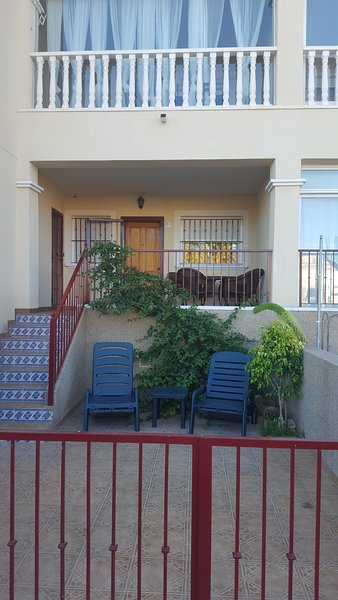 Sunny double terrace with dining set and sun loungers.