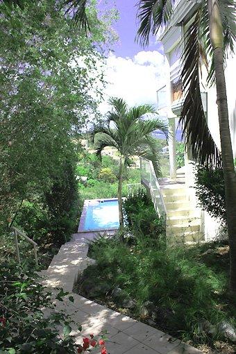 Una pasarela de azulejos en la parte izquierda de la villa conduce a la unidad inferior y la piscina