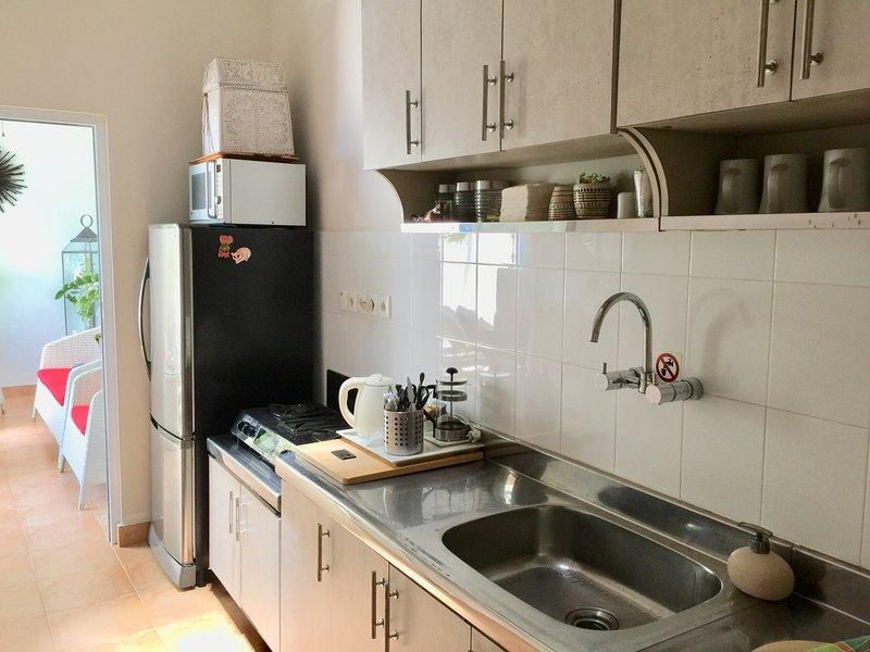 De la cuisine à la chambre extérieure, porte en verre de sécurité menant à la salle en plein air, des chaises longues et une piscine