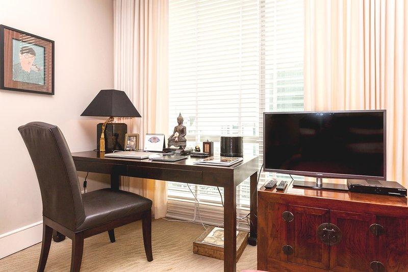 Habitación con cama doble, TV, escritorio y vestidor