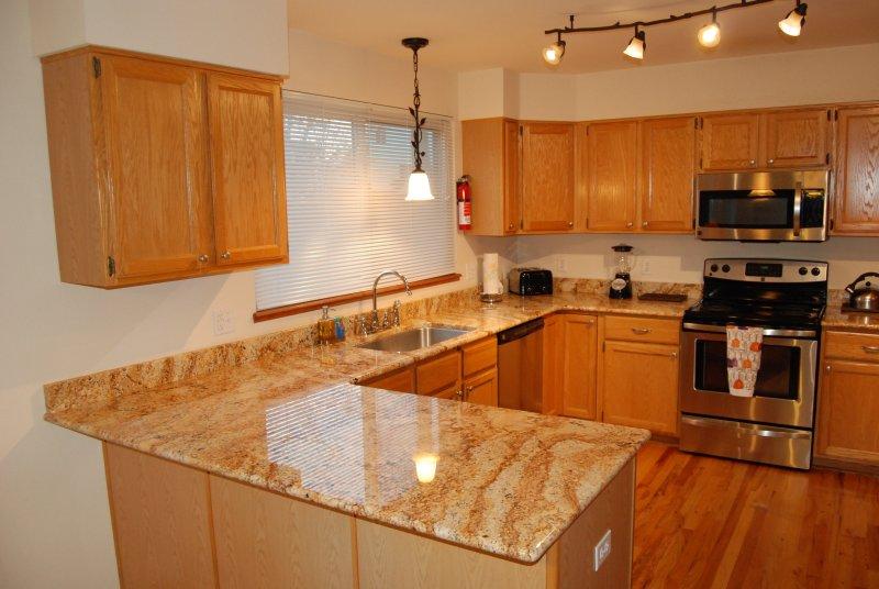 cocina tiene encimeras de granito y muchos accesorios de cocina