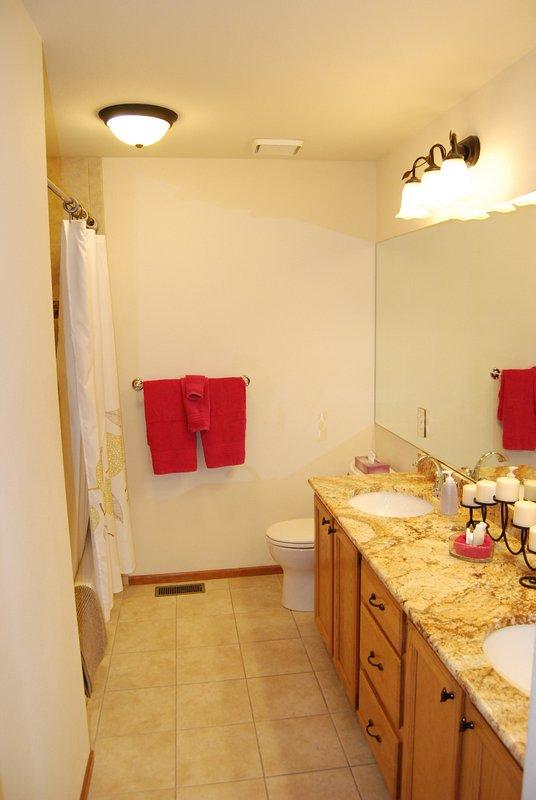 Gran sala de baño tiene dos lavabos y una encimera de granito