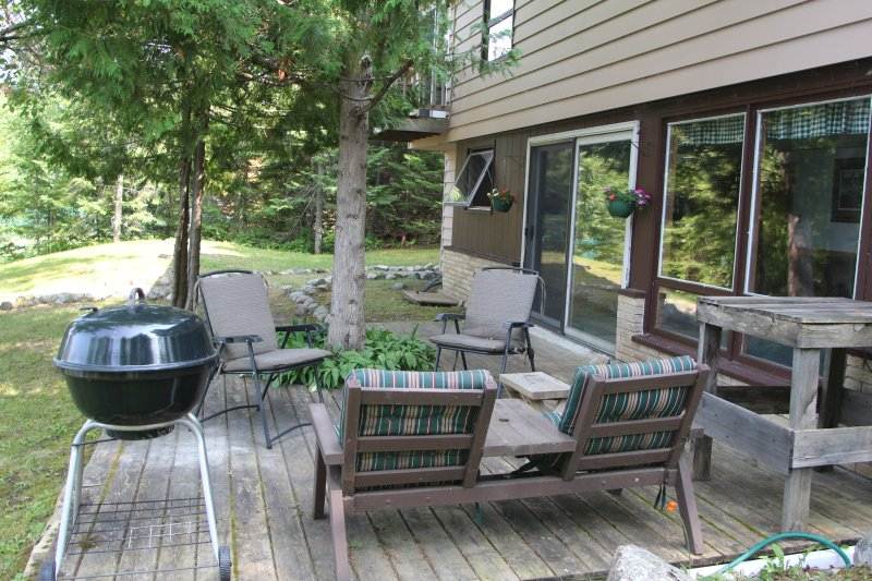 Deck/patio and grill. Small observation deck of the master bedroom visible in the background