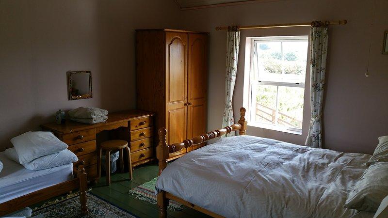 Geräumiges Hauptschlafzimmer mit Doppelbett und separatem Einzelbetten.