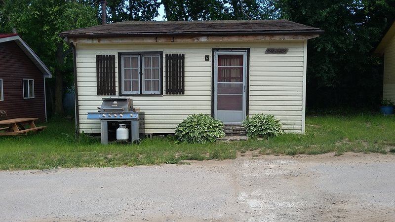 View of front of cottage, BBQ, and outdoor picnic bench (not shown), and yours to use.