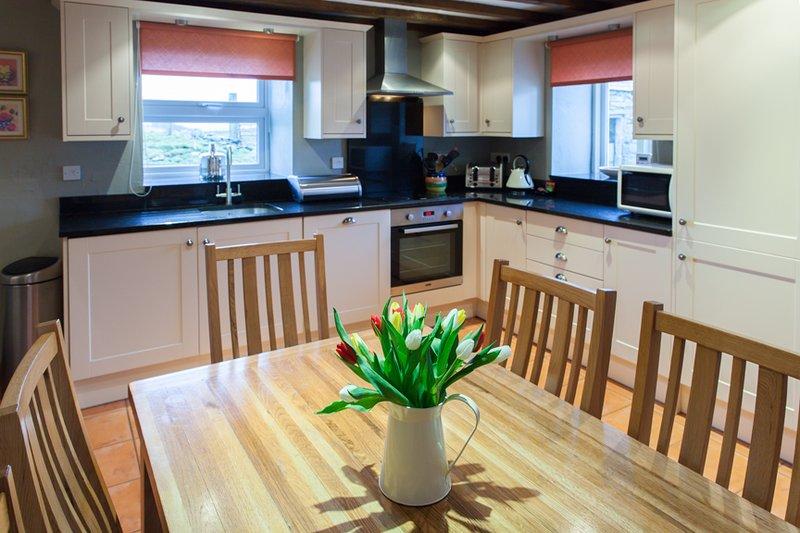 Cozinha com bancadas em granito e teto com vigas.