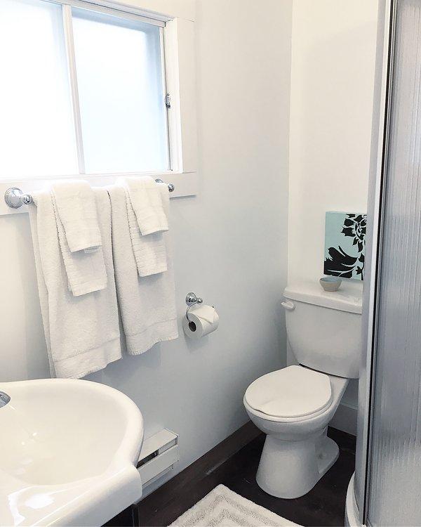 El baño tiene una cabina de ducha de esquina.