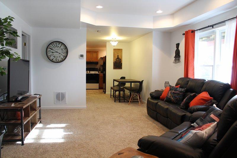 Grande salle de séjour avec de nouveaux fauteuils inclinables en cuir